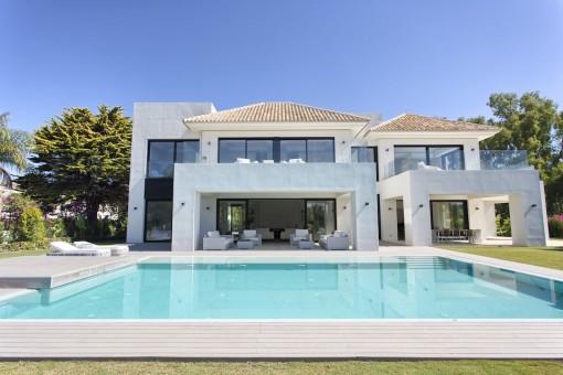 Vista exterior de la villa moderna con gran piscina